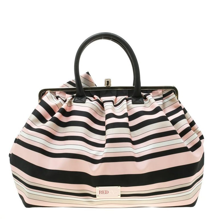 This RED Valentino bag is a must-have! It is expertly designed from striped fabric and gold-tone hardware to form the frame top. The bag features a spacious canvas interior, two leather handles and a large bow detailed on the front.  Includes: Price