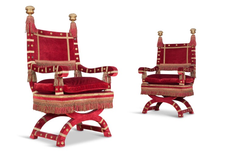 Hollywood regency style exuberant and decorative Pair of armchairs, Italy, 1940s.   The chairs are upholstered in a rich red velvet, with gold details and floss decorations.  The tops of the backrests are decorated with two large floral ornaments in