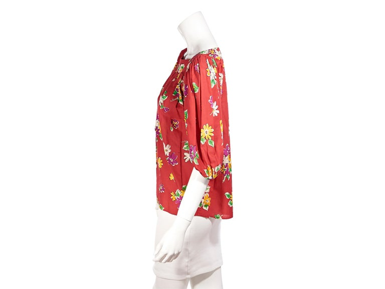 Product details:  Vintage red floral-printed blouse by Saint Laurent Rive Gauche. Bateau neckline. Puff shoulder dolman sleeves. Elasticated-trimmed cuffs. Slip-on style. Pair yours with denim shorts. Label size FR 38. 40