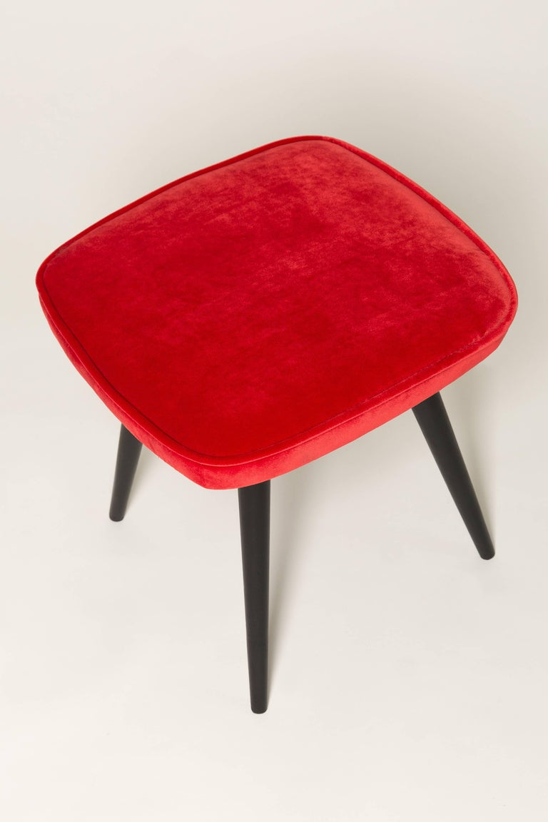 Stool from the turn of the 1960s and 1970s. Beautiful red velvet upholstery. The stool consists of an upholstered part, a seat and wooden legs narrowing downwards, characteristic of the 1960s style. We can prepare this pair also in another color of