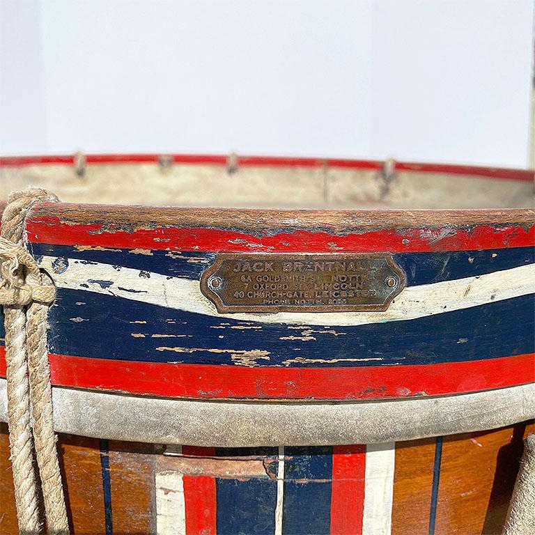 Important British drum by Jack Brentnall. In red, white, and blue, this lovely piece stands on a custom created stand making it perfect for use as a side table. The original plaque is intact and affixed to the side near the top. Ropes are tied in a