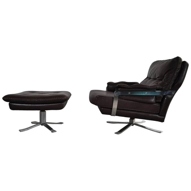 Reddish Brown Leather and Chrome Lounge Chair and Stool by Arne Norell For Sale