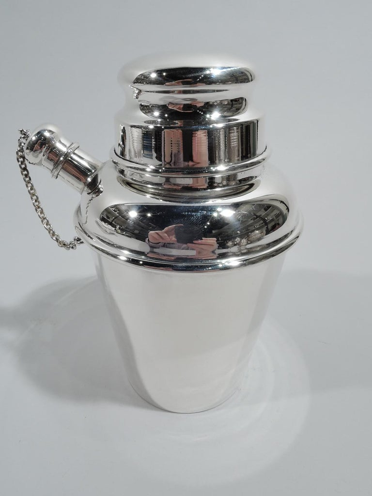 Mid-Century Modern sterling silver mini martini shaker. Made by Reed & Barton in Taunton, Mass., in 1951. Straight and tapering sides, curved shoulder, and short neck. Snugly fitting bun cover and stubby spout with chained ball cap. All the