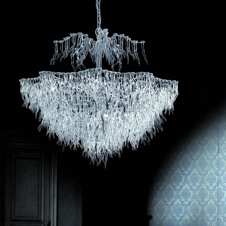 Inspired by the intriguing silhouette of corals, this enthralling chandelier boasts a silhouette comprising countless, flame-like elements in transparent glass that are all different from each other and create a splendid ensemble tapering downwards.