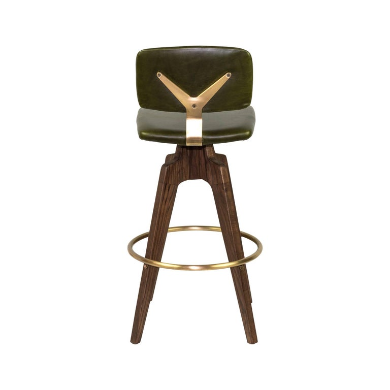 Swivel bar stool with walnut legs and brass accents. Seat and back upholstered in leather.
