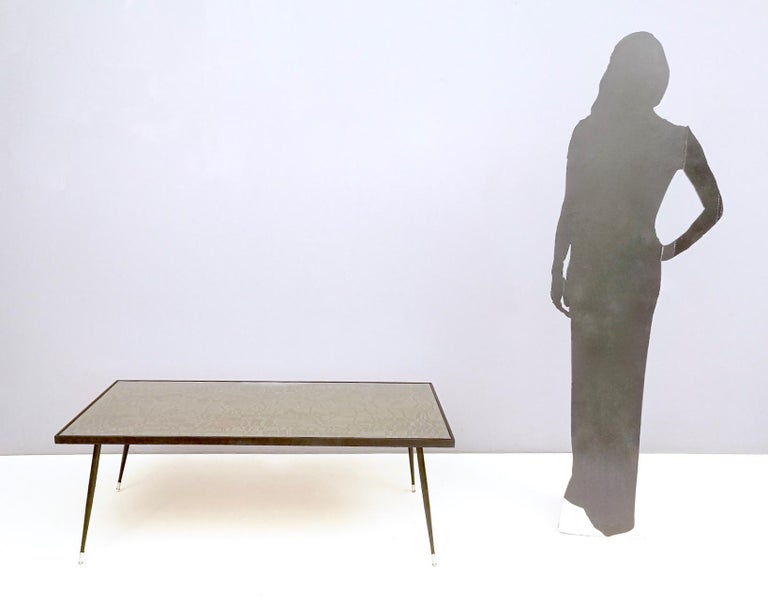 This coffee table is made etched brass and features varnished metal and brass legs and ebonized beech edges. It also has a glass top to protect the engraved brass, which is wonderful, refined and archaic. This coffee table recalls Marino Marini's