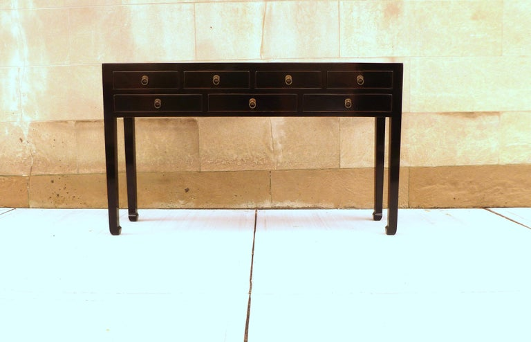 A simple and elegant black lacquer console table with seven drawers and brass ring pulls, beautiful color, form and lines. We carry fine quality furniture with elegant finished and has been appeared many times in