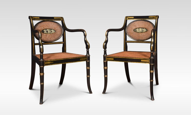 Refined set of eight English Regency style cane armchairs, Classic in form with an ebonized finish and original gold painted details. The backrest with central oval painting depicting three cherubs, each chair has a different design. Above cane work
