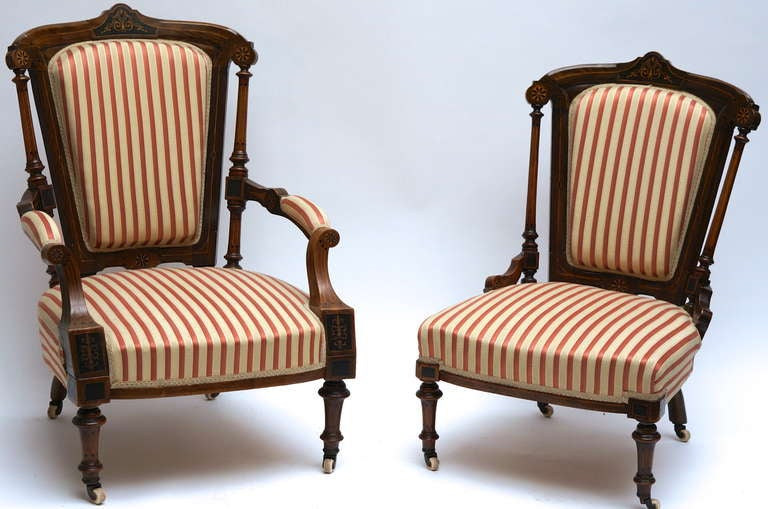 A refined set of two Victorian low chairs, one with armrests and a settee, all executed in walnut, with inlaid panels of blackened pearwood and intricate Hollywood inlaid lines and motives on the top rail and on the armrest fronts. Resting on