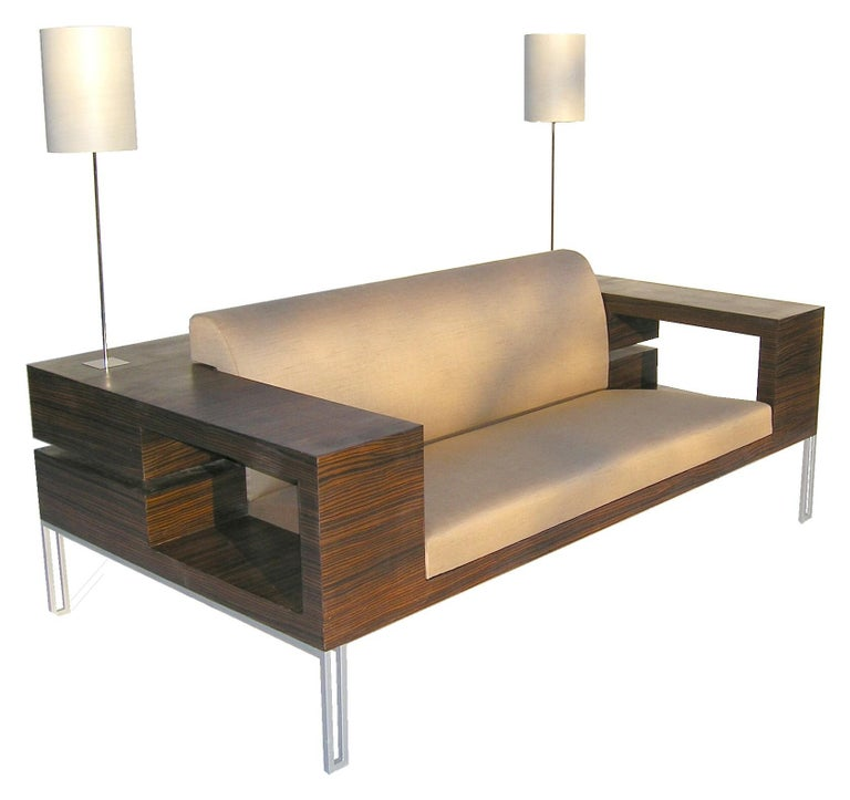 The idea for this sofa was to put together in one furniture all what you need to surround a sofa, a chest of drawers, side tables and standing lights. This furniture is made in Macassar ebony and has six drawers in the back and larges armrests. This