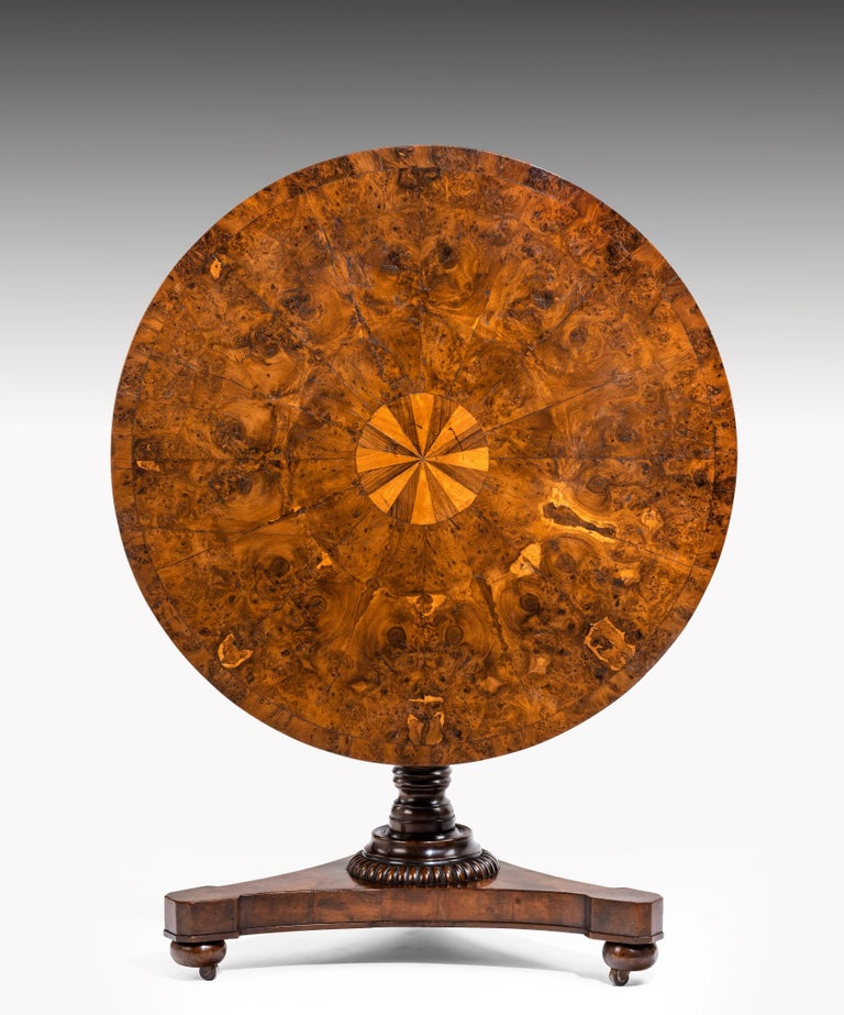 A Regency period centre table veneered in burr yew; the table's top segment veneered in yew wood with a central inlayed circle of satinwood and rosewood; the table is raised on a turned stem which terminates in a triform base.  This centre table