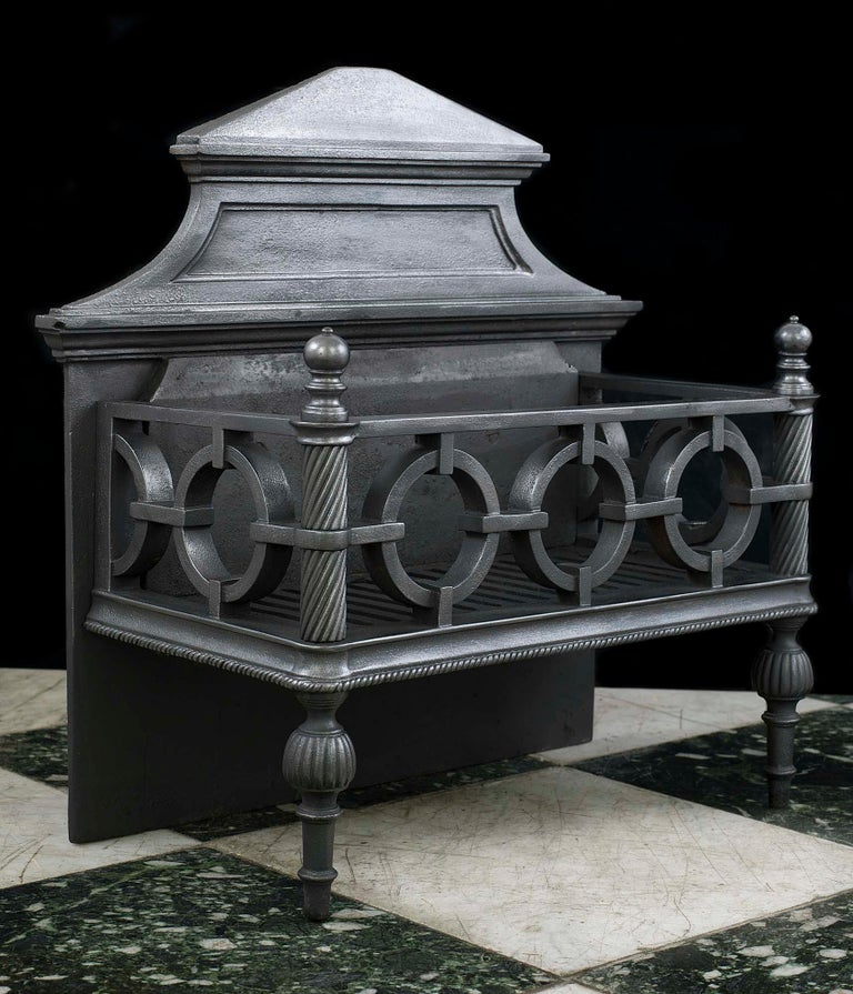 A heavy Regency cast iron fire grate with a pediment backplate, linked circles forming the grate front and sides, sturdy barley twist standards topped by small round finials and terminating in reeded bulbous, pegged feet, English, circa 1830.