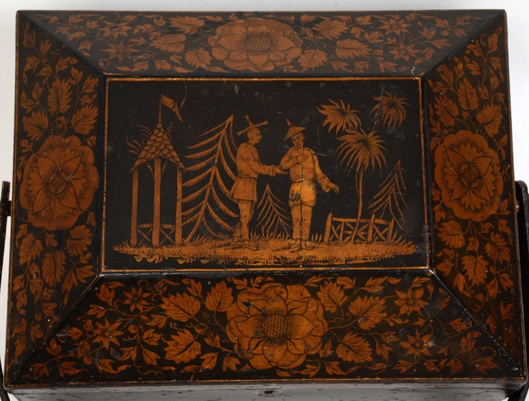 Regency chinoiserie decorated penwork sewing box with swing handle, circa 1810. With original paper lined interior. The central cartouche is decorated with a whimsical, imaginary, semi-tropical scene of two men wearing oriental clothing standing in