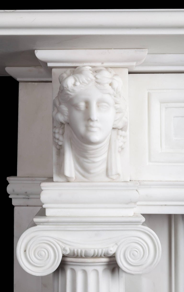 An early 19th century statuary Carrara marble mantelpiece of large-scale and great quality. The jambs with full rounded freestanding fluted ionic columns. Upon these are end blocks finely carved with classical busts. Recessed frieze panels flank an