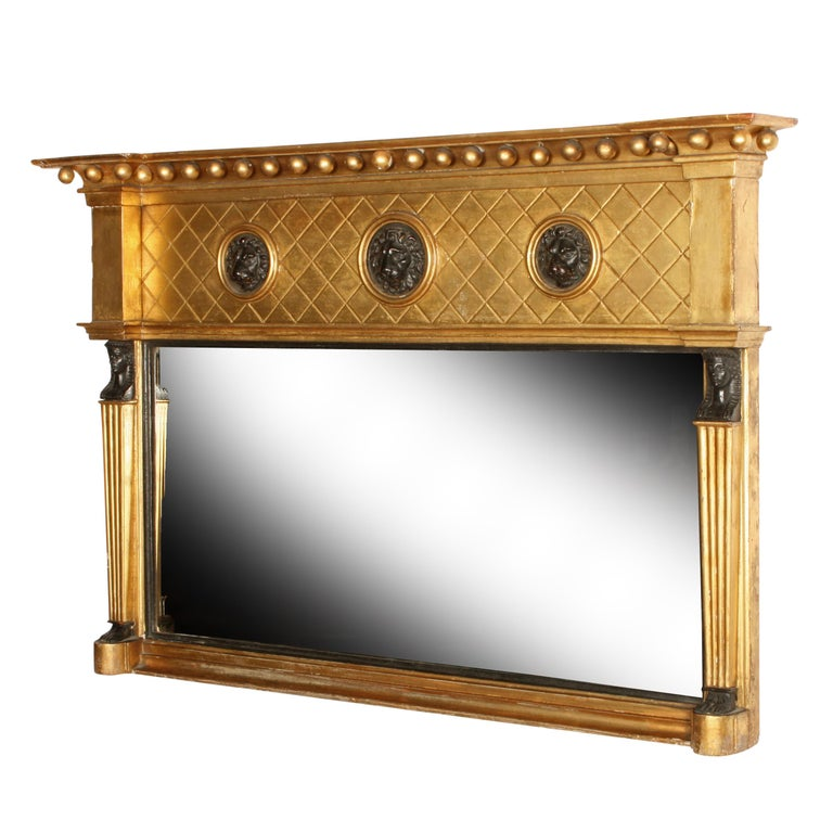 Regency giltwood overmantel mirror.   An early 19th century Regency carved gilt wood and gesso overmantel mirror.  The frame is decorated with three lion masks in the top frieze and Egyptian figures flanking the mirror plate.  The mirror has