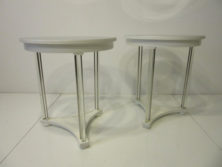 A pair of egg white wood side tables with glass and silver toned metal rod legs having a inset round glass and mirrored top sitting on wood bun styled feet. A sharp simple looking pair of tables that glistens in the light refracting off the heavy