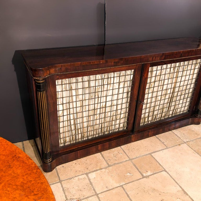 A fine English Regency rosewood grill door credenza with turret corners, turned bulbous and gilded fluted supports, on a plinth base. The brass grill doors enclosing an interior with shelf.