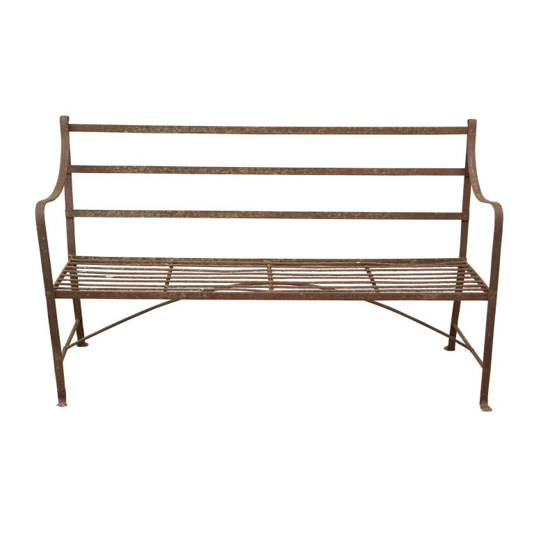 Regency iron garden bench features a riveted-construction reeded iron frame standing on subtle lion's paw feet. Dating from circa 1810-1830, this bench's patina is exquisite from decades of natural weathering and use.