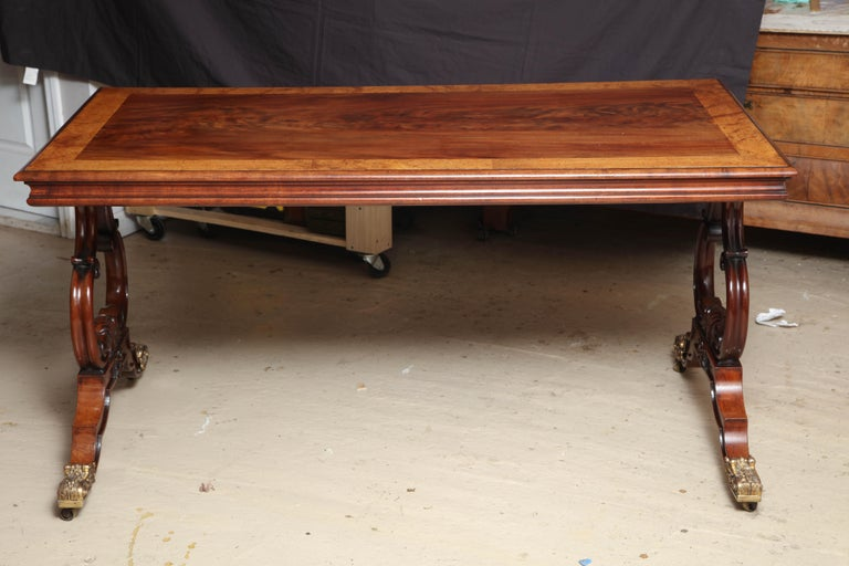 Handsome table which can be used as a desk or center table; the top is a single piece of flame mahogany with amboyna cross banding; raised on lyre-form supports and raised on finely chased scroll-form caps and casters.