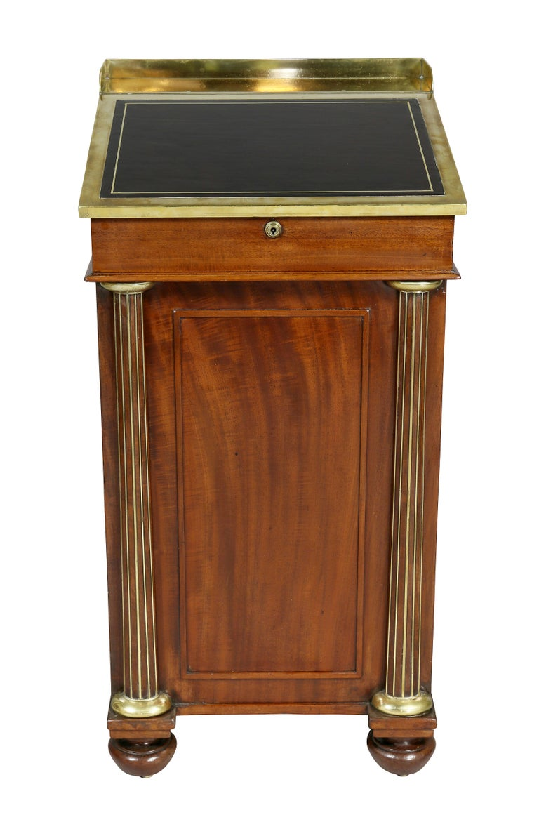 With a slant lid adjustable hinged leather writing surface with interior, over real and opposing false drawers and brass-mounted columns ending on bun feet. Keys. Provenance; Apter- Fredericks, London.