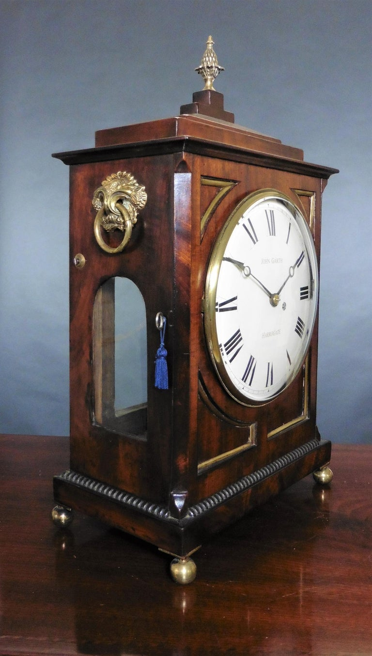 Regency bracket clock by John Garth, Harrogate  Mahogany case standing on a stepped base with ribbed decoration and standing on four brass ball feet, chamfered top surmounted by a brass pineapple finial.  Cast brass bezel with bevelled glass