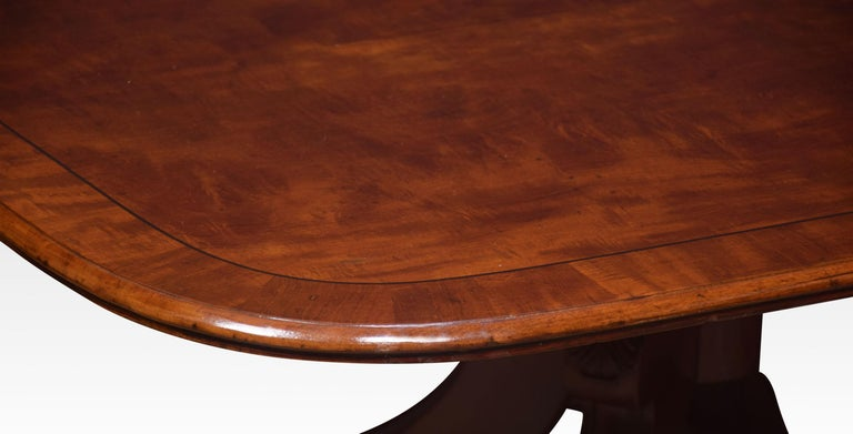 19th Century mahogany coffee table, the rectangular top and crossbanded edge enclosed by ebony stringing. Raised on a pedestal base and four outswept legs. This table has been reduced to coffee table height Dimensions Height 19.5 Inches Width 54
