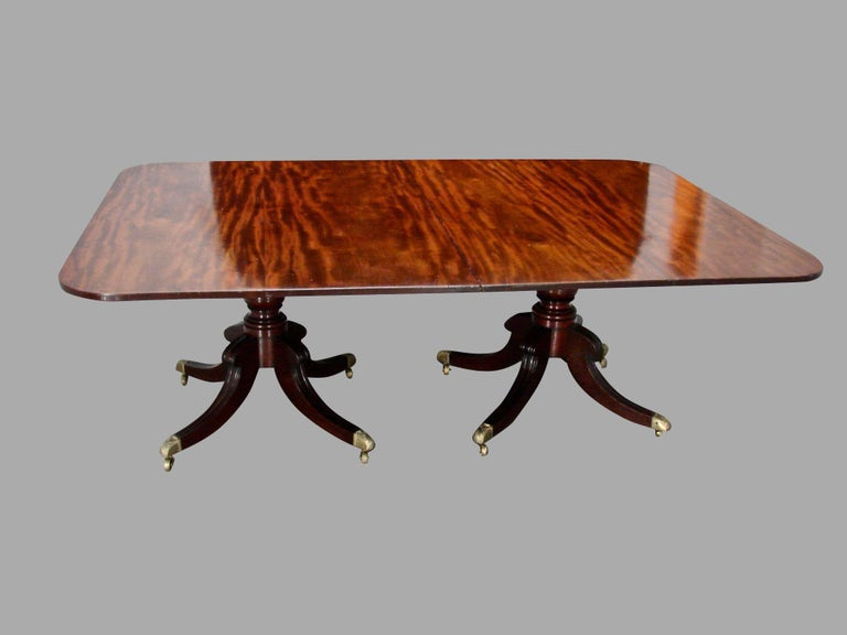 An English Regency period 2 pedestal dining table with a single leaf, the solid well-figured mahogany top supported on a turned standard with molded downswept quadripartite base supported on brass caps with casters. Great wide boards, circa 1825.