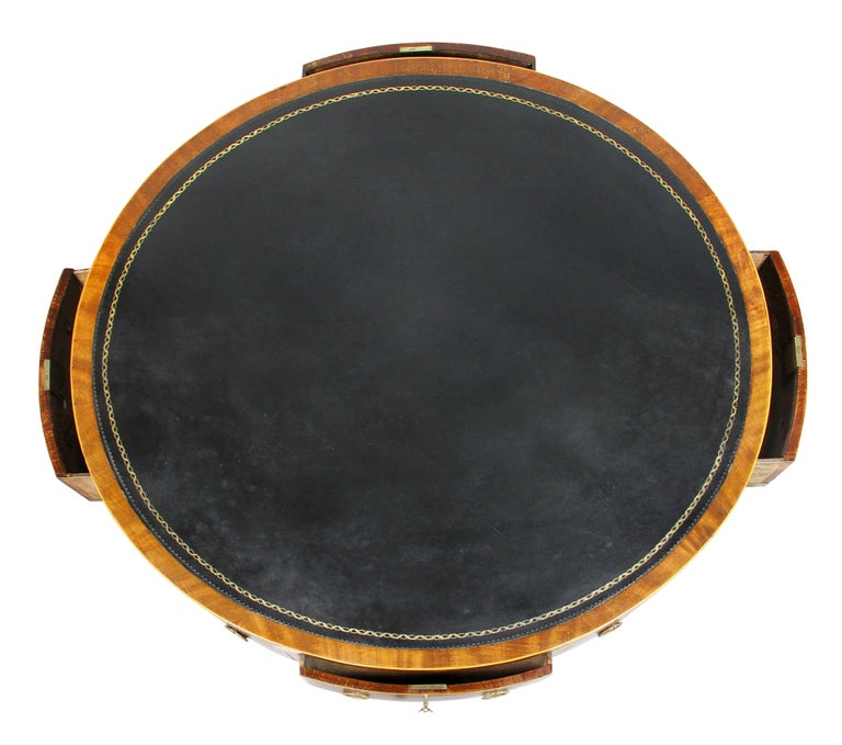 Circular top with crossbanded edge and black tooled leather over alternating drawers with ring handles, raised on a turned support and three saber legs with casters.