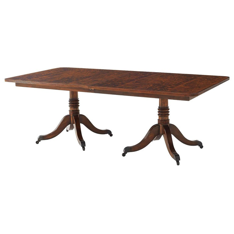 A mahogany veneer and solid twin pedestal extending dining table, the crossbanded reeded edge top with rounded corners opening to accommodate a matching leaf, above a banded frieze on two gun barrel turned columns each terminating in four downswept