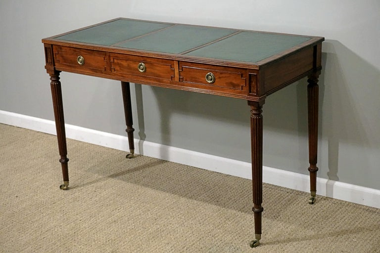 Regency mahogany writing table with leather desktop and brass accents and castors.