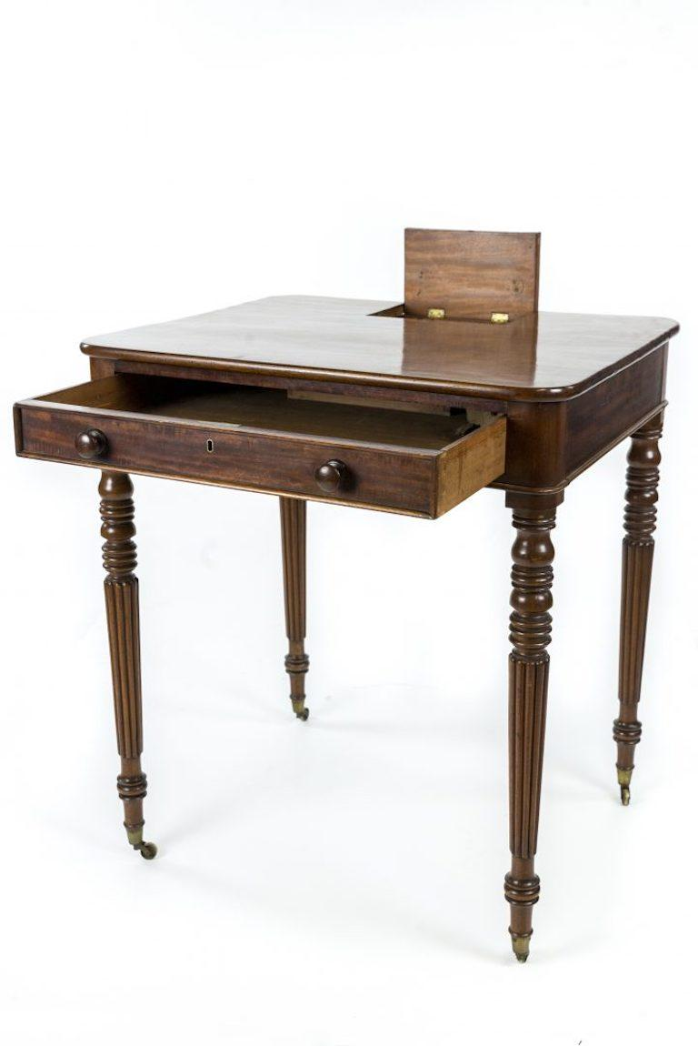 A Regency mahogany writing table, signed 'Gillows, Lancaster', 'the rounded corner top with hinged compartment above a frieze drawer and reeded tapering legs   Gillows of Lancaster and London, also known as Gillow & Co., was an English furniture