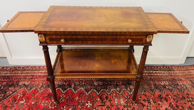A spectacular Maitland Smith Regency style end or side table or tray table. This elegant table features brass inlay on a Fine Mahogany hand-wood carving design. The table has two side extensions . Each extension is leather tooled with leather gold