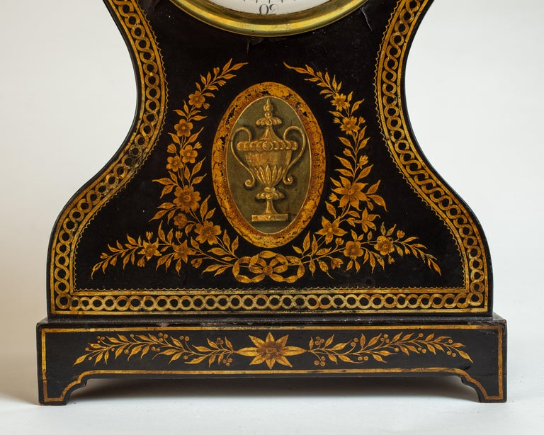 The waisted sides surmounted by a brass urn finial, above a rectangular base raised on bracket feet, decorated with braided border and depictions of floral swags, garland, and hunt trophies, the porcelain dial with Roman numerals and Arabic numerals