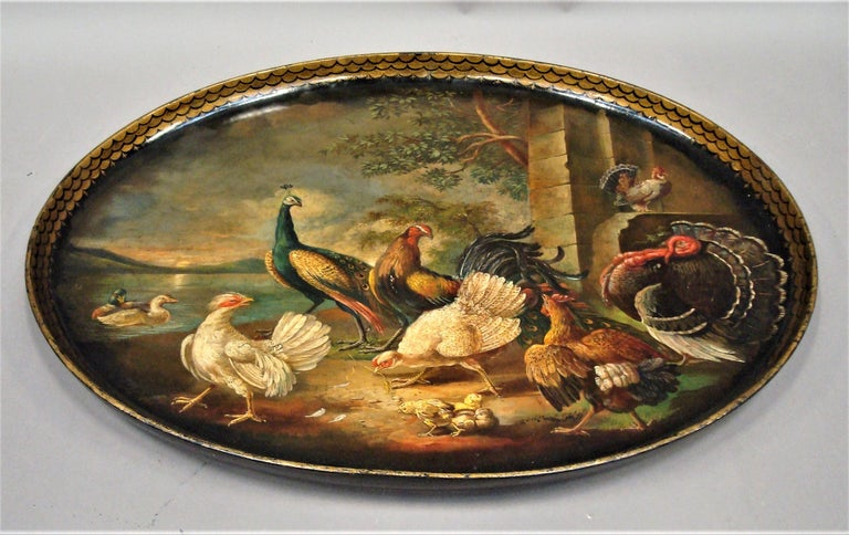 Exceptional RegencyPapier Mâché tray of oval form; the raised edge decorated with a gilt fish scale design surrounding a finely painted scene of peacocks turkeys and hens with chicks in a classical landscape setting with a stone building with ducks