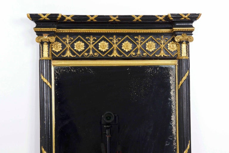 This elegant Regency period pier mirror is a practice in contrasts, utilizing a pure black pigment over gesso against the bright silvered glass and vibrant gilded highlights.  Borrowing from the French, the mirror incorporates a twisting and