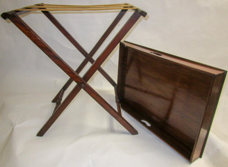 Regency period mahogany butlers tray on stand featuring a rectangular shaped tray with surround gallery. A slight slope terminates to one side with handles on either side. On folding X-frame stand with heavy woven straps to accommodate the tray.