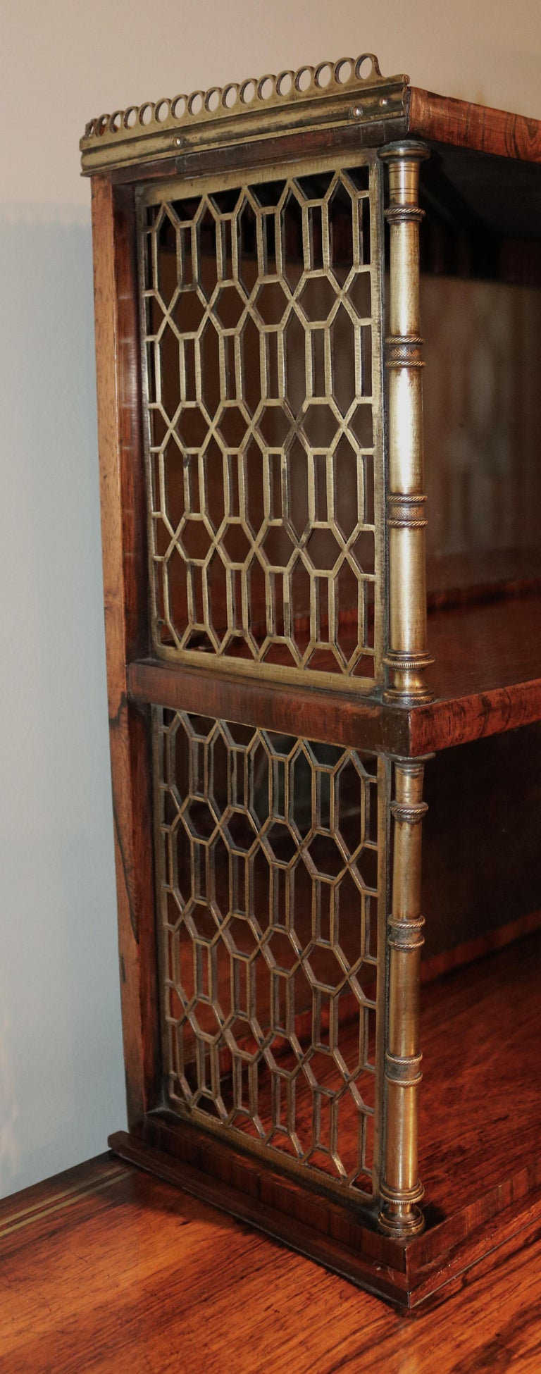 An important early 19th century Regency period rosewood and brass inlaid breakfront chiffonier, having mirrored galleried upper part with fretwork and column sides, above gilt brass edged top and frieze drawers with inlaid swag and phoenix panels,