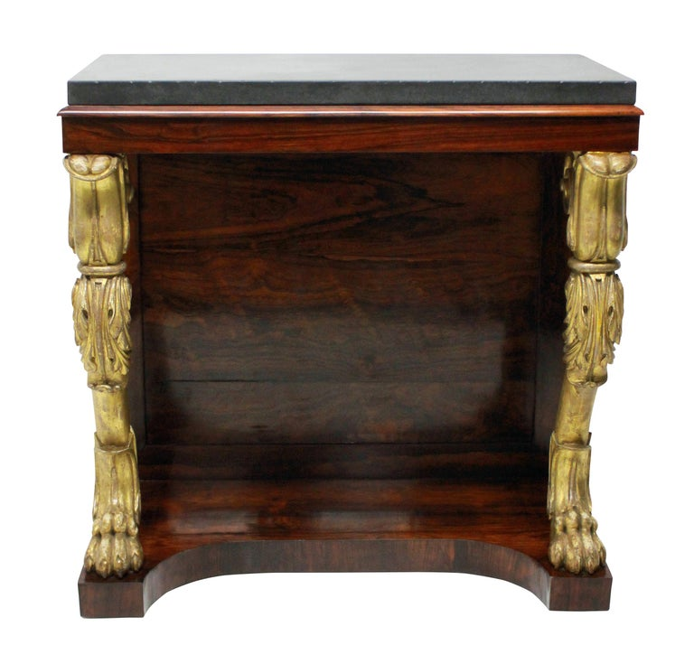 An English Regency console table in rosewood, with two carved and water gilded monopodia legs. The top of Belgian marble.