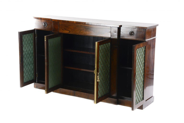A very good quality Regency rosewood credenza, the breakfront top above a central drawer and four cupboards with metal lattice and silk backing on a plinth base.