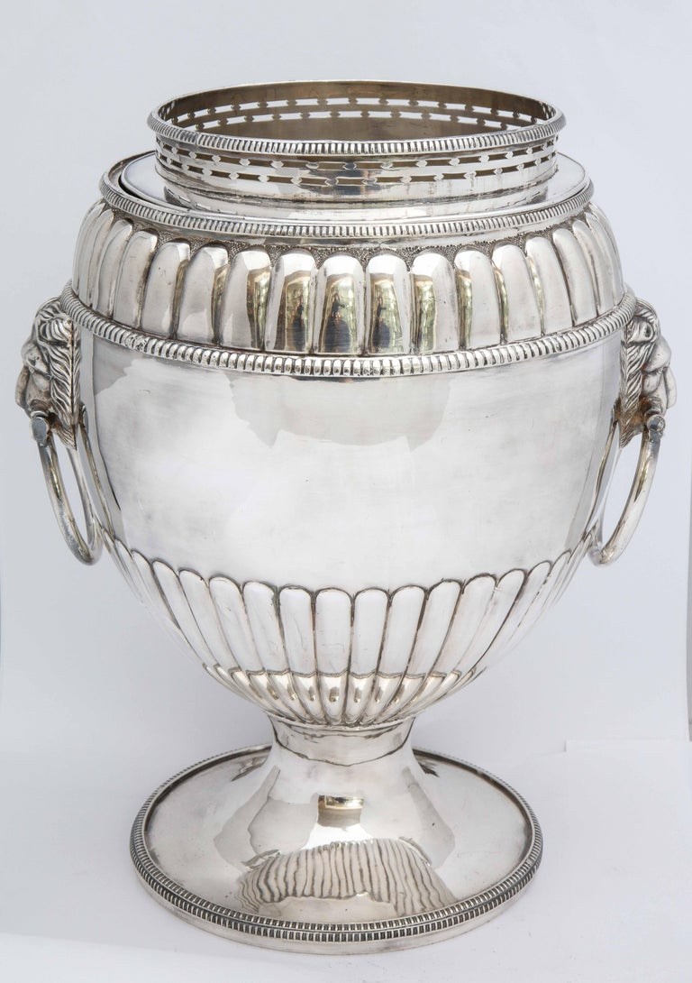 Regency, Sheffield plated, pedestal based wine cooler, England, Ca. 1840's. Has lion's head handles, with each lion having a movable ring in its mouth. Cooler has original insert and removable collar. Fluted design; vacant cartouche. Rim is very
