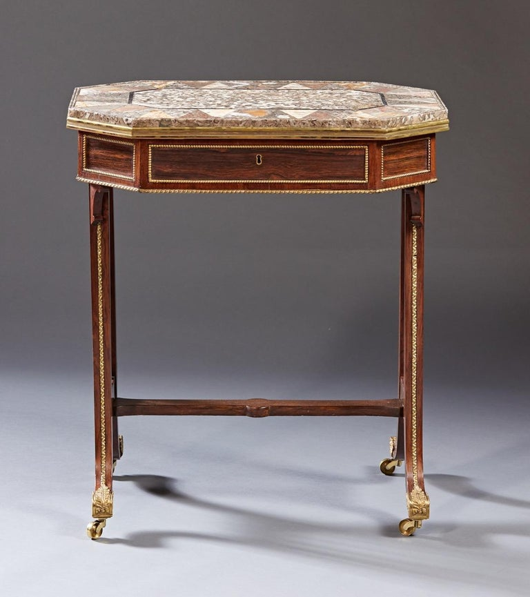 A rare side table attributed to Gillows of London and Lancaster having a specimen inlaid marble top rests on a conforming octagonal shaped case in rosewood with a single drawer on down swept legs. The entire case and legs are mounted with gilt
