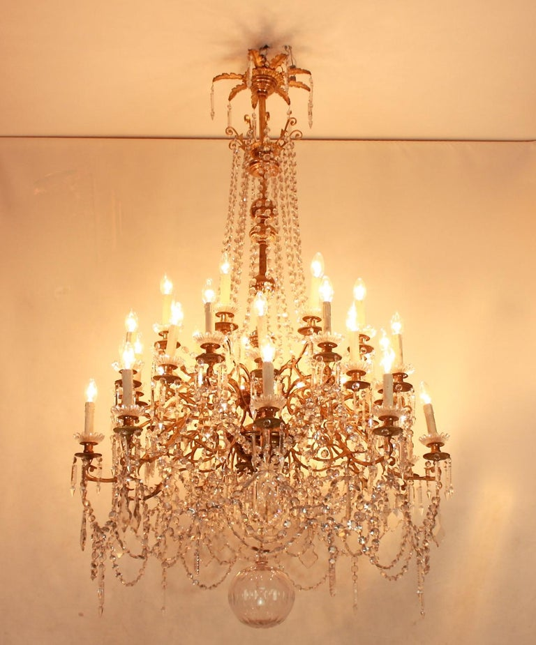 Monumental Regence-style thirty-six light gilt bronze and crystal-cut chandelier from circa 1860. The massive central baluster stem finely cast with mascarons, arabesque ornament and acanthus leaves, issuing thirty six scrolling foliate candlearms