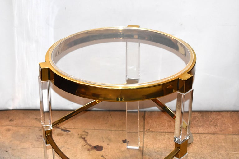 Pair of Lucite and brass side tables in the Regency style designed by Charles Hollis Jones in the 1960s. The tables have a beautiful ornate brass base with a thick banded top, the Lucite legs are very substantial and command attention, they can be