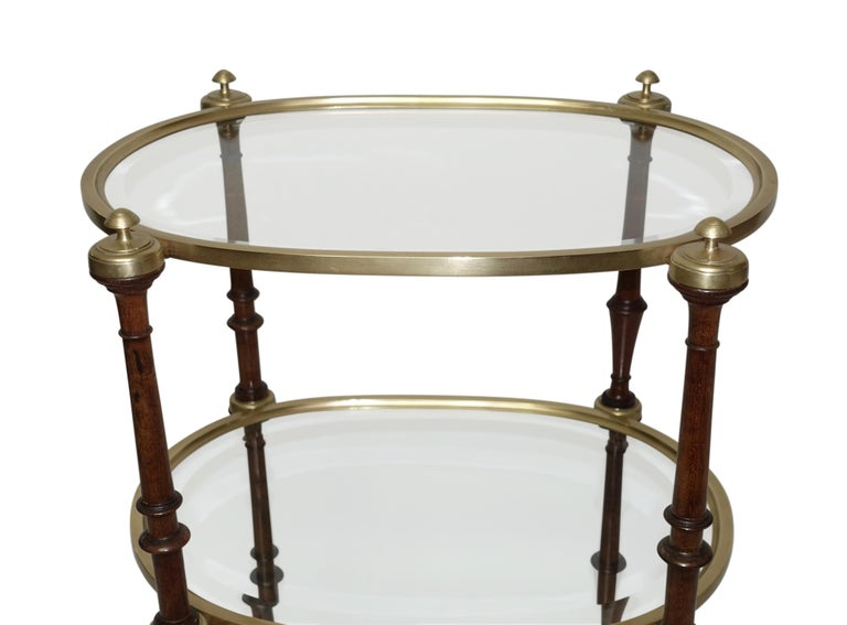 Mahogany Regency style brass three-tier side table with beveled glass top and lower shelves turned mahogany supports with brass trim ending with brass sabots, English, circa 1860.