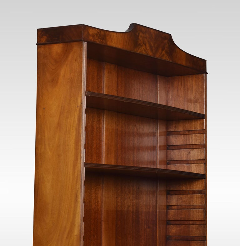 Regency style mahogany bookcase, The shaped cornice above four adjustable shelves. The base section fitted with a pair of paneled doors opening to reveal a fitted interior. All raised up on splayed feet.