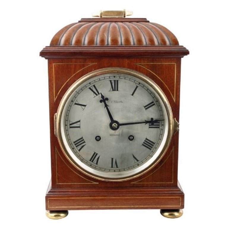 A late 19th to early 20th century Regency style mahogany cased bracket clock.  The clock has an eight day movement that strikes a coiled gong on the hour and half hour.  The silverised dial has Roman numerals and the retailer's name