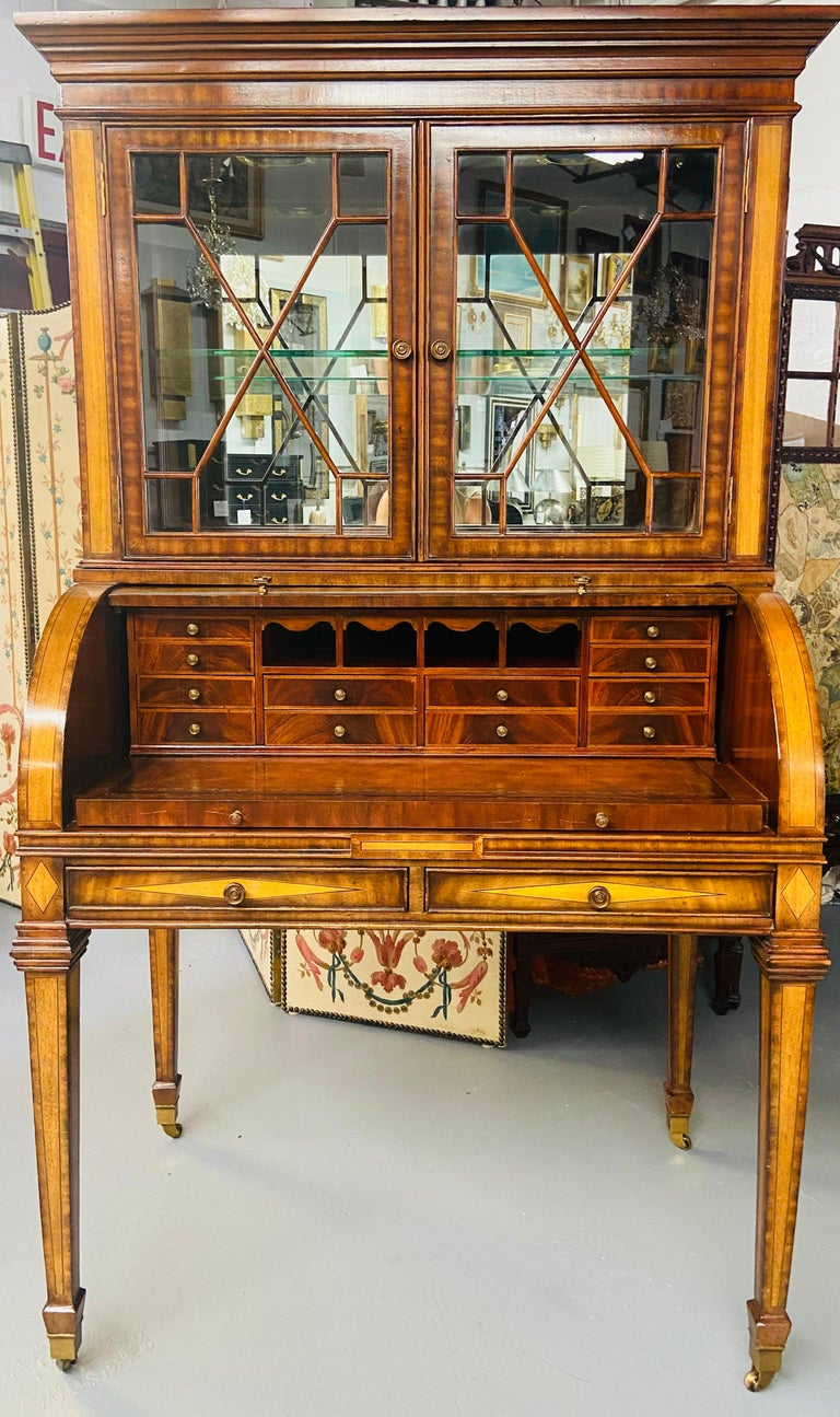This stunning Regency style Maitland Smith flame mahogany secretary desk has two parts. The upper part is a two sectional glass door cabinet with one glass shelf and two adjustable inside lights. The bottom part features a slant lid covering