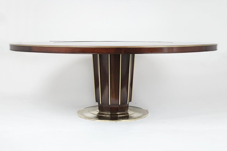 This Regency style dining table by Bill Sofield for Baker is made out of mahogany wood and brass and has been completely restored. This dining table has been newly stained in dark mahogany color with gilt accents and lacquered finish. This