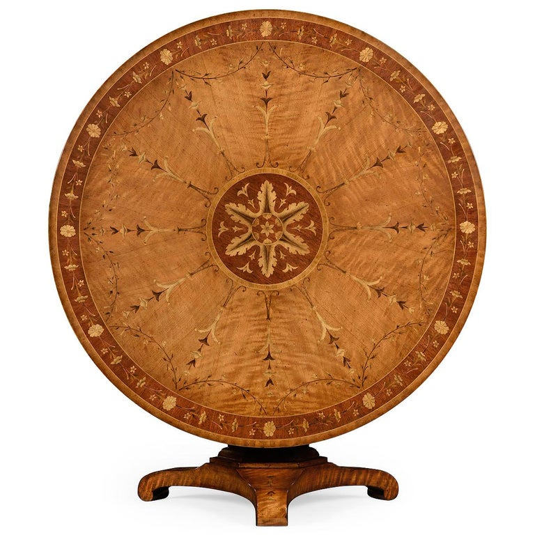Regency style round tilt-top satinwood center table (or dining table) with neoclassic designs and a scrolling trefoil base.