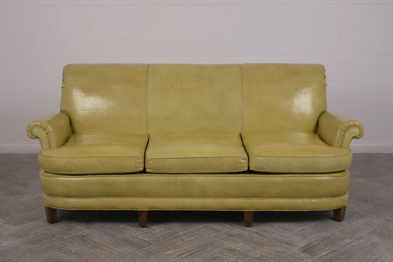 Vintage 1960s Regency style three cushion sofa has walnut stained wooden legs. The sofa has the original upholstered leather in a lemon green color. The sofa is comfortable and ready to be used in any home for years to come.  Measures: Arm height